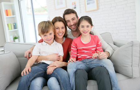 35847432 - cheerful family at home sitting in sofa